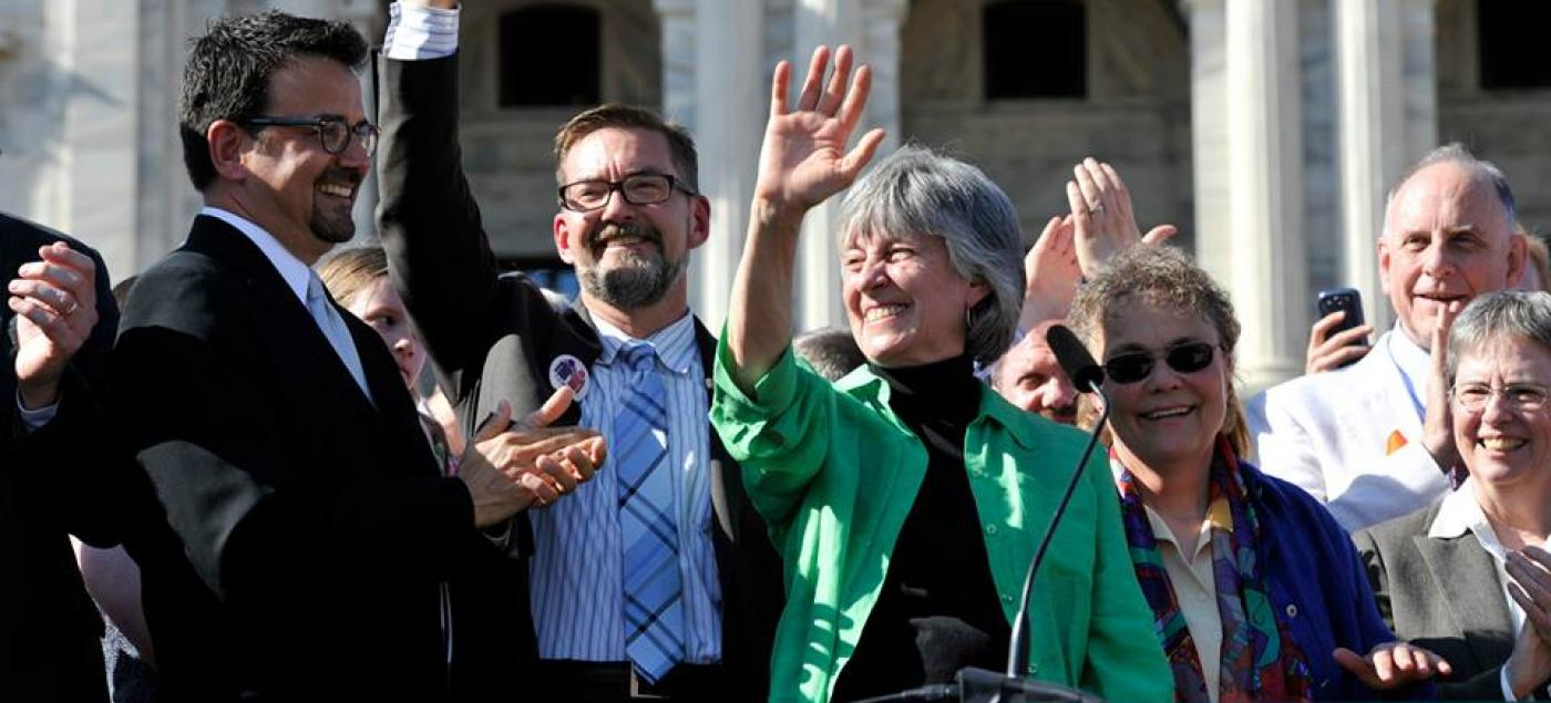 Representative Karen Clark and Senator Scott Dibble waive from the Capitol Steps.