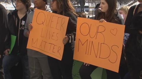 """Emotional day at the capital."" A crowd stands holding orange signs which read ""Queer lives matter"" and ""Our minds."""