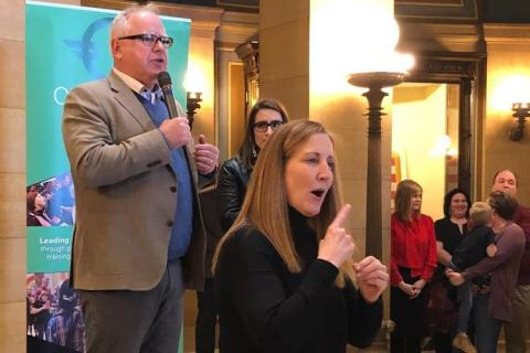 With the aid of a sign-language interpreter in the foreground, Walz speaks to about 100 LGBTQ activists and their supporters.