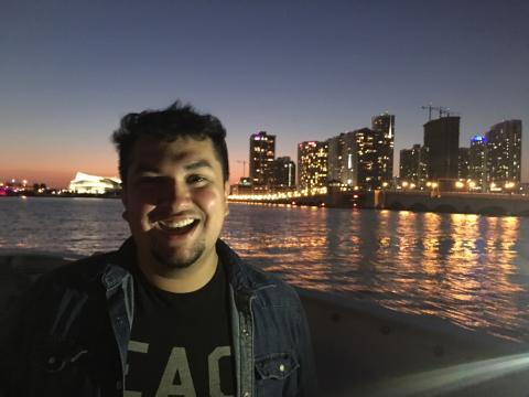 Photo of Junior Avalos next to a river and city skyline.
