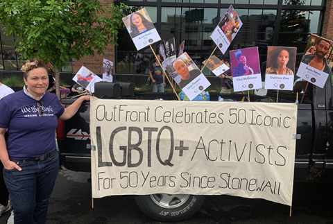 "Monica Meyer, wearing one of Outfront Minnesota's ""We The People means everyone"" t-shirts, stands beside a banner which reads ""OutFront Celebrates 50 Iconic LGBTQ+ Activists For 50 Years Since Stonewall,"" behind which photos of several of those icons are displayed on picket signs."