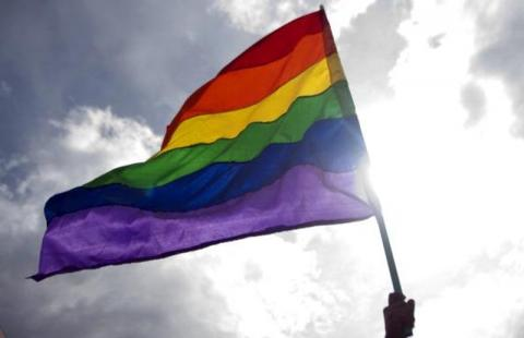 """Some young people are being forced by desperate parents to undergo a widely discredited therapy."" A rainbow flag waves in front of the sun. (Getty)"