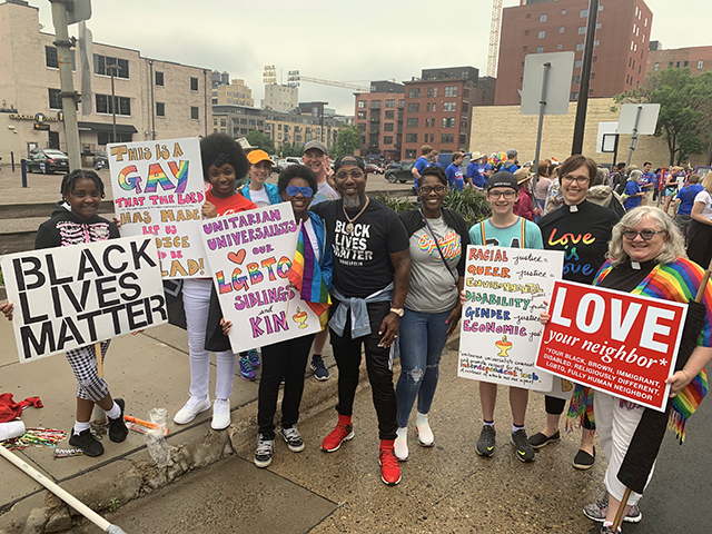 "A small crowd stands with colorful shirts and signs reading slogans such as ""Black Lives Matter,"" ""Love they neighbor*,"" ""Unitarian Universalists love our LGBTQ siblings and kin,"" and ""Love is Love."""