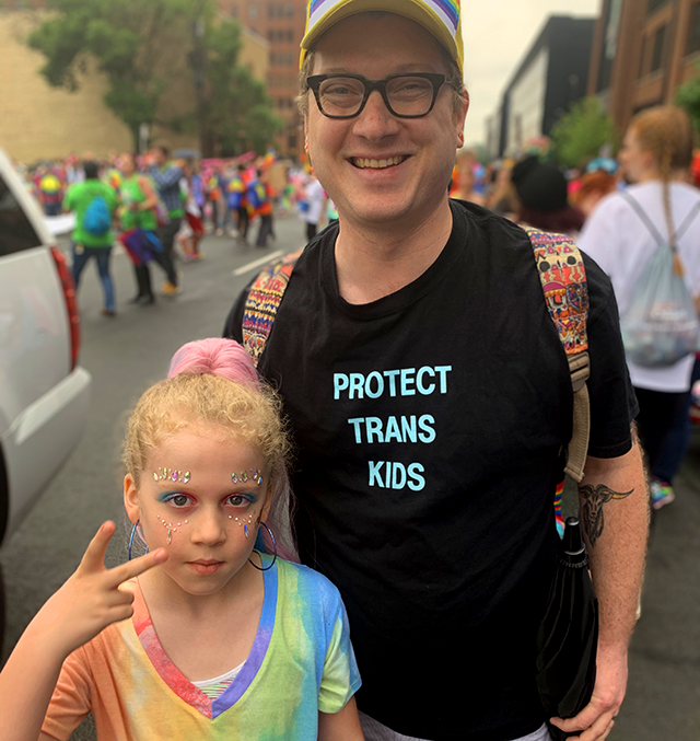 "Dave and Hildie Edwards face the camera. Dave, wearing a shirt that reads ""protect trans kids,"" smiles. Hildie, dressed in rainbow fashion, displays a peace sign to the camera."