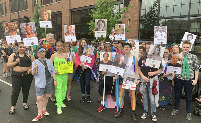 A small crowd stands together, each holding picket signs featuring influential figures in the LGBTQ+ community.