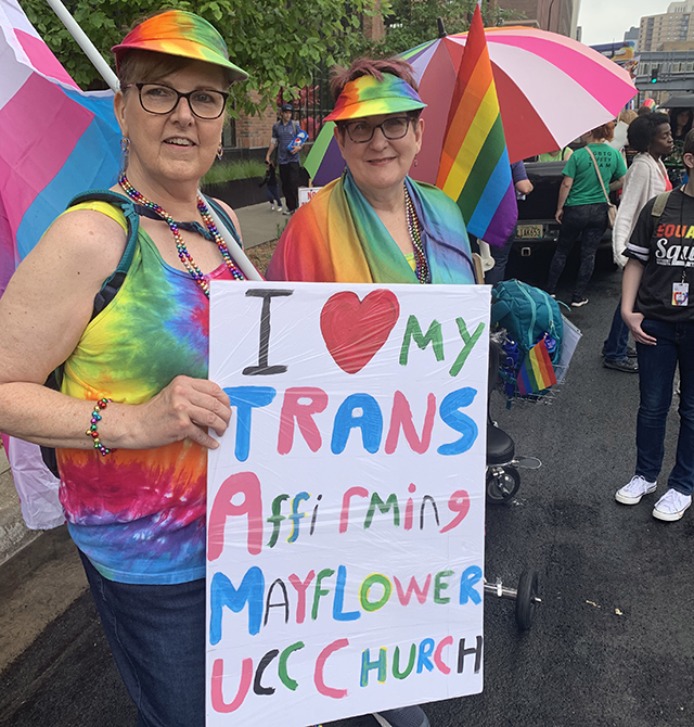 "Stephanie and Carla Peck smile towards the camera. Dressed in rainbows and holding a transgender pride flag, they display a sign that reads ""I love my trans affirming Mayflower UCC Church."""