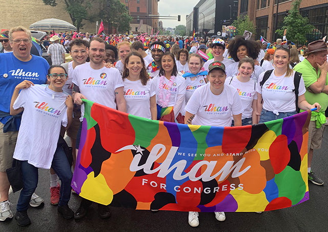 "Supporters of Ilhan Omar, each wearing a shirt featuring her name written in a scrawling rainbow font, stand together holding a banner covered in colorful patterns and reading ""We see you and stand with you"" and ""Ilhan for congress."""