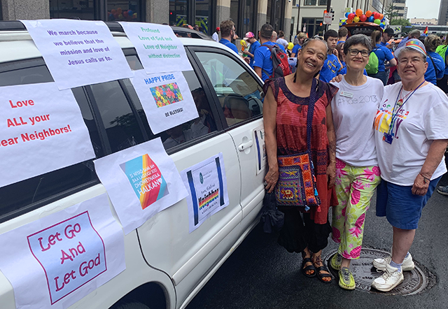 Marianne Graham, Kathleen Olsen, and Cheryl Maloney stand beside a van with several posters across its side.