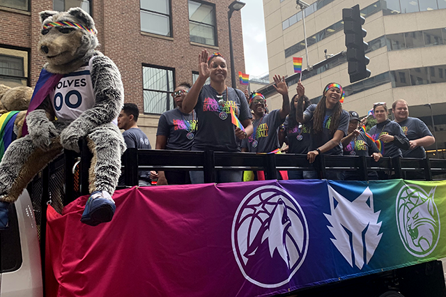 A float with a rainbow banner along its side featuring the logos of sports teams such as the Minnesota Timberwolves and Minnesota Lynx carries several waving individuals. The Timberwolves mascot, bearing a rainbow flag and headband, sits at the edge of the vehicle.
