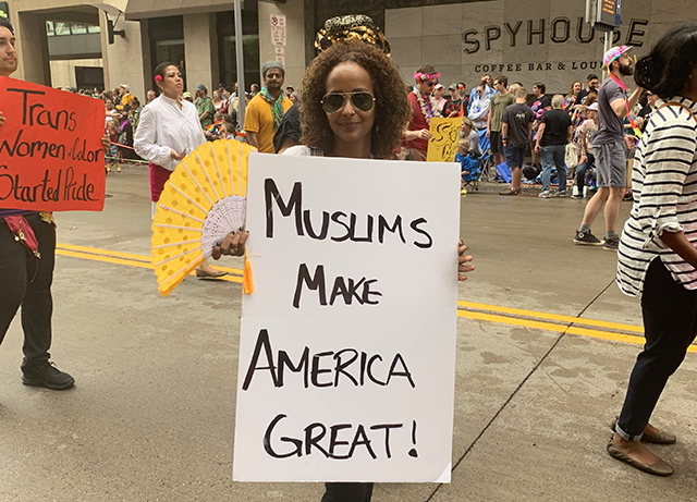 "Leila Ali displays her ""Muslims make America great!"" sign to the camera while holding a yellow folding fan. Another poster reading ""Trans women of color started pride"" is visible in the background among the marchers as well."